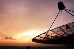在暮色天空背景的卫星盘剪影 免版税库存照片