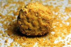在曲奇饼粉末背景的一个黄色曲奇饼  库存照片