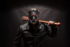 在曲棍球面具的精神分析的凶手在黑背景 库存照片