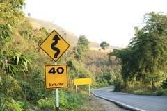 在曲线山路旁边的路标 免版税图库摄影
