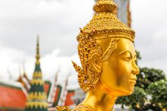 在曼谷玉佛寺的金黄Kinnari雕象 库存图片