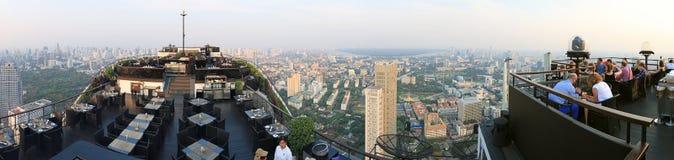 在曼谷的日落从屋顶上面酒吧观看了用享受场面的许多游人 库存图片