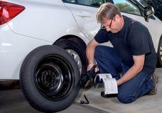 在替换一个备用轮胎的读书指示 库存图片