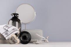 在最低纲领派样式的典雅的装饰梳妆台-黑花瓶,玻璃,化妆辅助部件,毛巾,镜子,在灰色的木心脏 库存照片