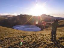 在最后冰河时期和拍照片期间,在一个更高的地方的一个男性身分由Jiaming湖由冰河运动形成了 免版税库存图片