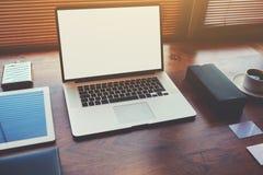 在最新的一代膝上型计算机的桌上的宽广的办公室年轻总经理,咖啡杯,数字式片剂 图库摄影