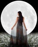 在月亮前面的妇女。 库存图片