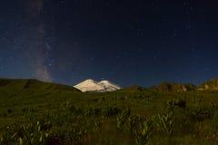 在月光、银河星和土星的斯诺伊山Elbrus在晚上 免版税库存照片