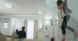 在有一个大生活和白色台阶的一个现代房子里跑下来到一楼的两个孩子早晨到他们 股票视频