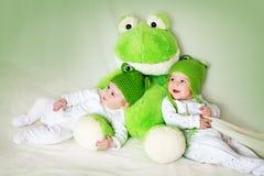 在有一个软的玩具的青蛙帽子的两个逗人喜爱的婴孩 库存图片