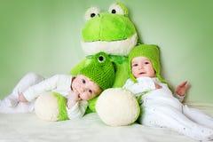 在有一个软的玩具的青蛙帽子的两个逗人喜爱的婴孩 免版税图库摄影
