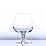 在有一点蓝色光的空的科涅克白兰地一口威士忌酒与反射 库存照片
