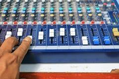 在有与浅景深的尘土精选的焦点老的一种混音器控制设备的手 库存照片