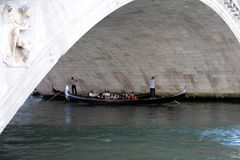 在有两名平底船的船夫和他们的长平底船的Rialto桥梁下 免版税图库摄影