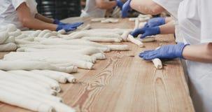 在有准备面团的蓝色手套的大面包店产业两的面包师,揉面团准备面包 4K 股票视频
