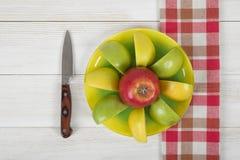 在有刀子的一个茶碟在它旁边和在顶视图的方格的厨房桌布计划的苹果 图库摄影
