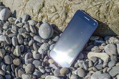 在有卵石花纹的海海滩的智能手机 免版税库存照片