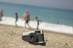 在有卵石花纹的海滩的减速火箭的照相机 免版税库存图片