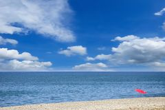 在有卵石花纹的海滩的唯一伞反对美丽如画的多云天空 图库摄影