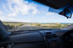 在有压低沿海路的仪表板的汽车里面 库存图片