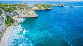 在有后边美丽的棕榈的海洋晃动在努沙Penida海岛,印度尼西亚上的Atuh海滩 免版税库存照片