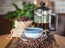 在有咖啡和法国人新闻的一杯附近驱散的咖啡豆 免版税库存照片