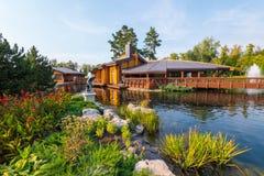 在有喷泉的公园筑成池塘在有一个夏天大阳台的一家餐馆中间在一边和美丽的花 免版税库存照片