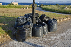 在有塑料垃圾袋和海景的希腊环境美化 库存照片