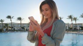 在有大海背景浏览互联网的水池边附近的微笑的妇女使用智能手机,通过她移动 股票视频
