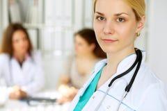 在有她的同事和患者的一个医院办公室医治妇女或护士在背景中 关心眼睛医疗保健卫生学医学 图库摄影