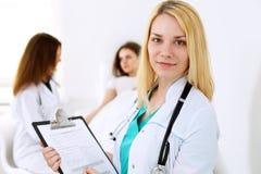 在有她的同事和患者的一个医院办公室医治妇女或护士在背景中 关心眼睛医疗保健卫生学医学 免版税库存照片