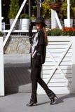 在有宽边缘进来的黑帽会议打扮的在黑长裤、一件时髦的灰色衬衣和毛线衣和时兴的女孩 免版税库存照片