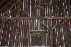 在有射线的一个老谷仓里面和垂直的委员会和雪 免版税库存图片