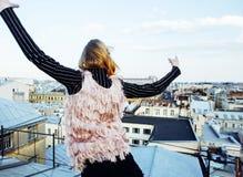 在有屋顶的上面的年轻俏丽的时尚夫人乐趣党时间,生活方式人概念 免版税库存照片