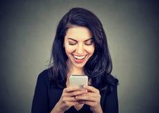 在有巧妙的电话的笑的妇女正文消息一次宜人的图交谈 免版税库存图片