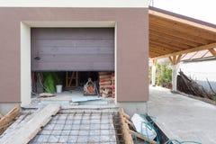在有建设中的基础的现代房子里打开车库门 库存照片