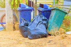 在有拷贝空间的城市堆黑垃圾袋塑料和四个垃圾箱肮脏的路旁 库存照片