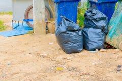 在有拷贝空间的城市堆黑垃圾袋塑料和四个垃圾箱肮脏的路旁 免版税库存图片