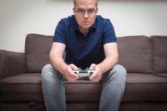 在有操纵台管理员的一个沙发安装的人在手和playin上 免版税库存图片