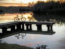 在有日落的码头停放的自行车 免版税库存图片