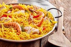 在有木匙子的金属平底锅供食的海鲜肉菜饭 免版税库存图片