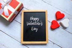 在有木handraft心脏和箱子的一个黑板写的愉快的华伦泰` s天 免版税库存图片