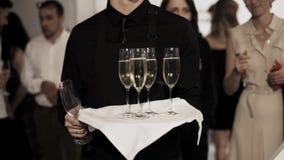 在有杯的黑拿着的盘子打扮的年轻侍者champaigne 影视素材
