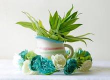 在有植物的一个陶瓷花瓶附近加冠花花束  库存图片