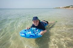 在有泳装、盖帽和水色的鞋子的逗人喜爱的白色被晒黑的孩子 免版税库存照片