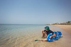 在有泳装、盖帽和水色的鞋子的逗人喜爱的白色被晒黑的孩子 免版税图库摄影