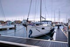 在有游艇、小船和新修造公寓的宗主港口停泊的游艇特写镜头在背景中 免版税库存照片