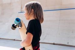 在有滑板的便服打扮的男孩在他的手立场在冰鞋公园在幻灯片旁边在晴朗 免版税图库摄影