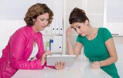 在有片剂个人计算机的办公室的两名妇女。 免版税库存照片