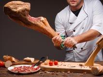 在有猪肉腿的厨房里烹调在手上 关闭与大型jamon的水平的图象在手上 免版税库存照片